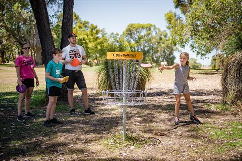Family practicing their disc golf technique, throwing light-weight plastic discs from a short distance into the basket in a treed surrounding.