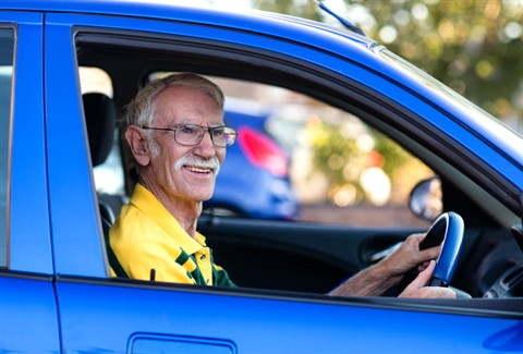 An older person sitting the drivers seat of a blue car looking out the drivers side window while holding the steering wheel